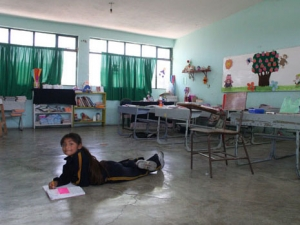 A girl drawing on the floor of her classroom